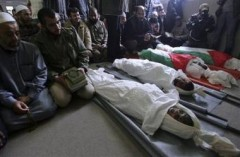 1217072465-palestinian-mourners-pray-next-to-the-bodies-of-four-youths.jpg