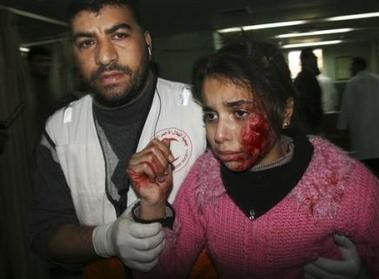 1526089156-a-palestinian-medic-walks-with-a-wounded-girl-who-according.jpg